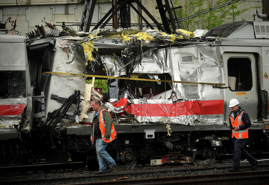 May 2013: Metro North train cars heavily damaged in Friday's derailment are pulled from the scene after being hoisted back on to the tracks in Bridgeport. Conn. on Sunday, May 19, 2013. Federal investigators have highlighted two pieces of rail they say were found broken at a joint bar at the accident scene in the area of the crash which injured 76 people. Photo: Brian A. Pounds / Connecticut Post
