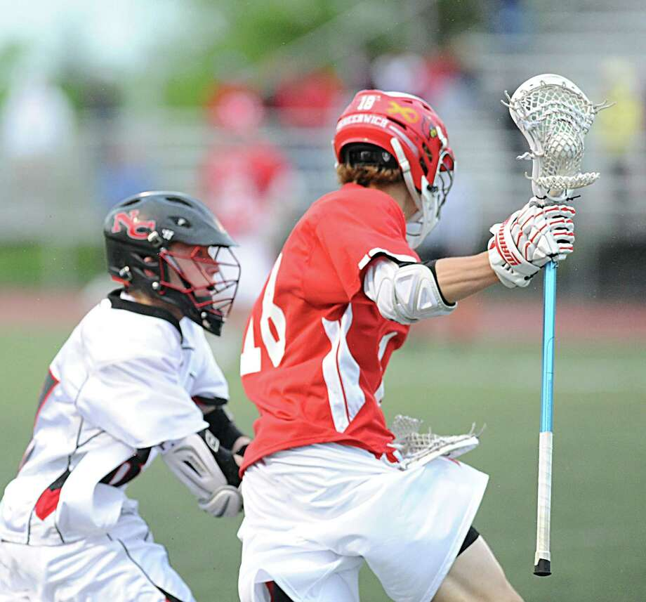 At right, Kelley Jay (# 18) of Greenwich gets past a New Canaan defender during the FCIAC boys high school lacrosse championship match between Greenwich High School and New Canaan High School at Brien McMahon High School in Norwalk, Friday night, May 24, 2013. New Canaan took the title defeating Greenwich, 8-5. Photo: Bob Luckey / Greenwich Time