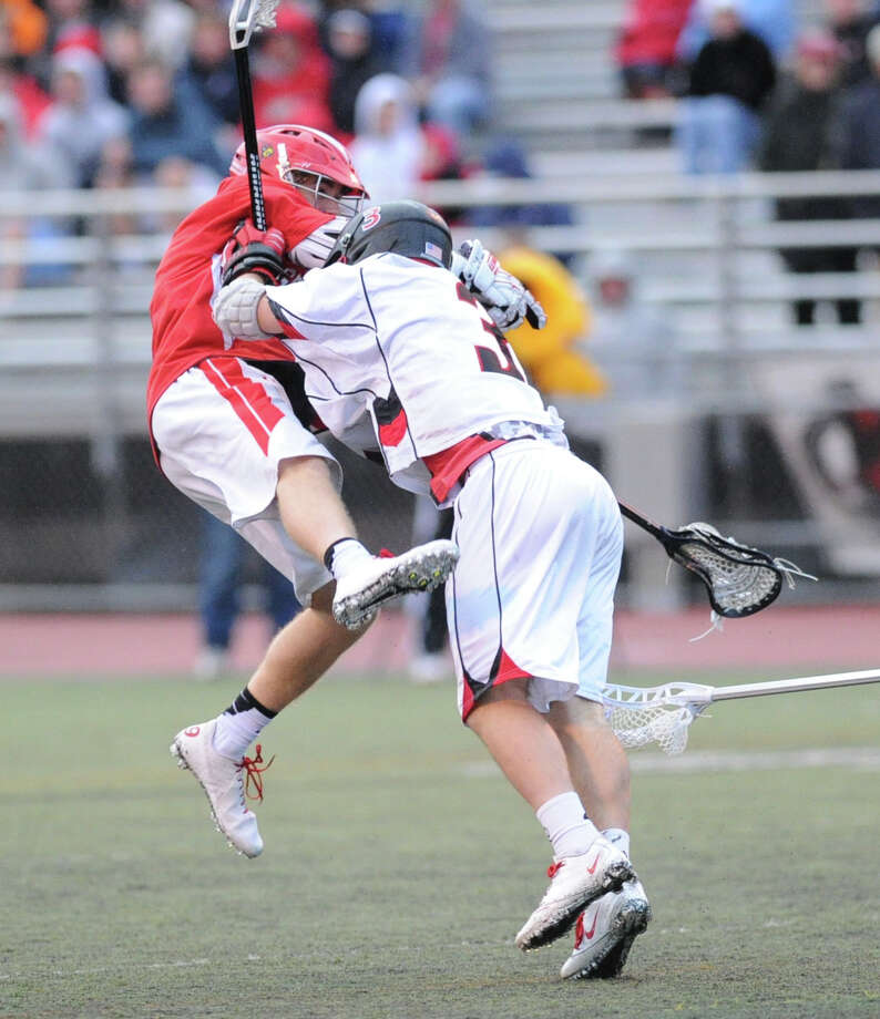 At left, James Paradise of Greenwich gets leveled by a New Canaan defender but manages to score a goal during the FCIAC boys high school lacrosse championship match between Greenwich High School and New Canaan High School at Brien McMahon High School in Norwalk, Friday night, May 24, 2013. New Canaan took the title defeating Greenwich, 8-5. Photo: Bob Luckey / Greenwich Time