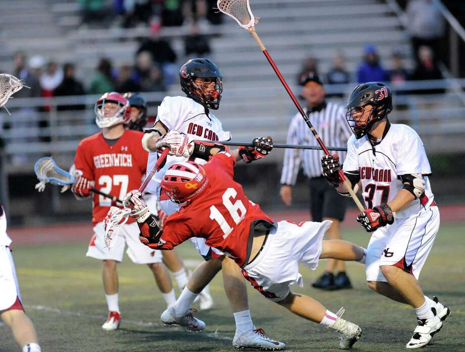 Matt Ellsworth (# 16) of Greenwich falls to the ground after taking a hit during the FCIAC boys high school lacrosse championship match between Greenwich High School and New Canaan High School at Brien McMahon High School in Norwalk, Friday night, May 24, 2013. At right is Eric Persky (# 37) of New Canaan and at left is Luke Finneran (# 27) of Greenwich. New Canaan took the title defeating Greenwich, 8-5. Photo: Bob Luckey / Greenwich Time