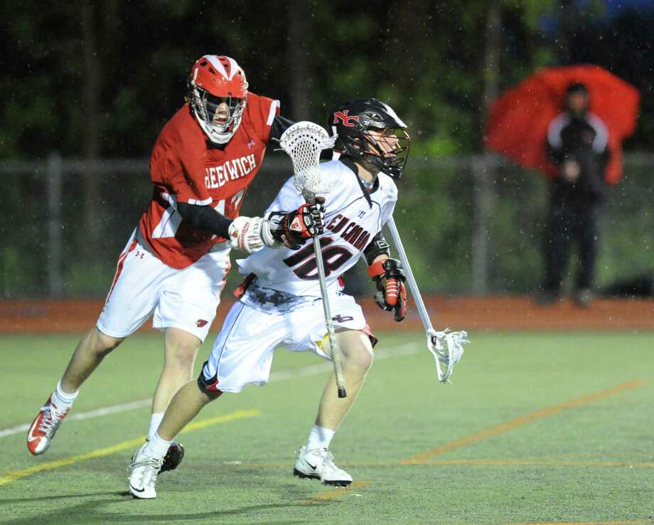At right, Peter Richardson (# 18) of New Canaan advances the ball during while being covered by Kelley Jay of Greenwich during the FCIAC boys high school lacrosse championship match between Greenwich High School and New Canaan High School at Brien McMahon High School in Norwalk, Friday night, May 24, 2013. New Canaan took the title defeating Greenwich, 8-5. Photo: Bob Luckey / Greenwich Time
