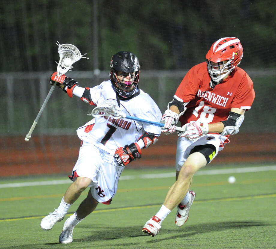 At left, Cole Turpin (# 7) of New Canaan advances the ball while being defended by Kelley Jay (# 18) of Greenwich during the FCIAC boys high school lacrosse championship match between Greenwich High School and New Canaan High School at Brien McMahon High School in Norwalk, Friday night, May 24, 2013. New Canaan took the title defeating Greenwich, 8-5. Photo: Bob Luckey / Greenwich Time