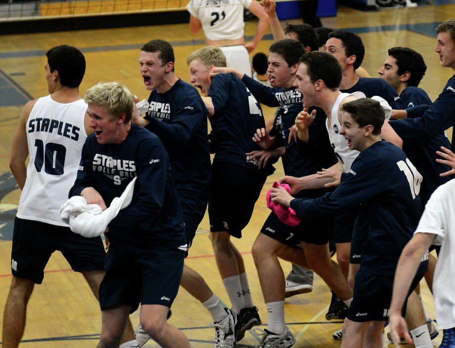 Staples team members rush onto the court to celebrate its win over Ridgefield, during FCIAC Boys' Volleyball Championship game action at Fairfield Ludlowe High in Fairfield, Conn. on Friday May 24, 2013. Photo: Christian Abraham / Connecticut Post