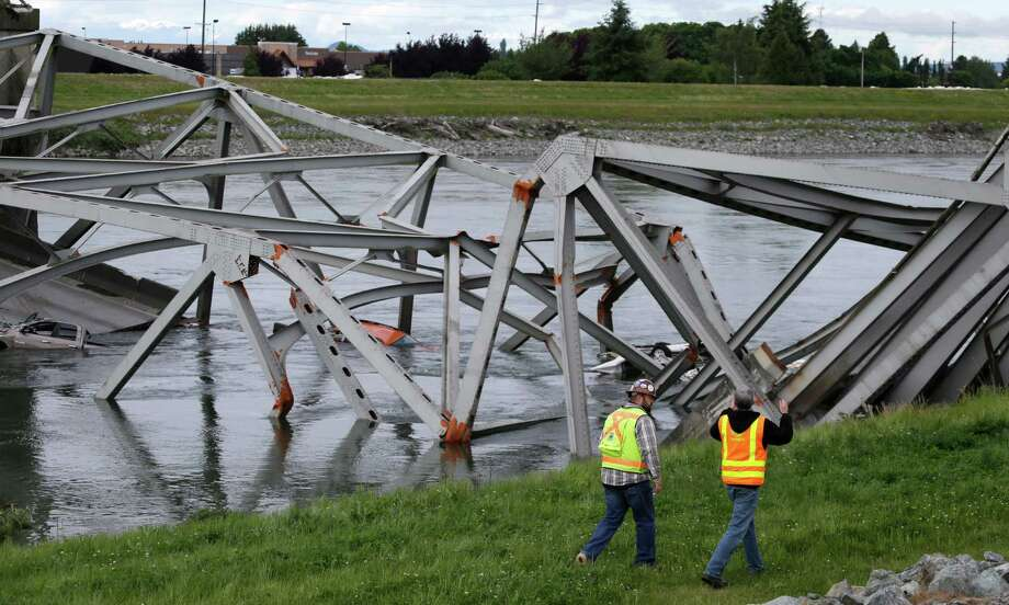 Workers walk past the collapsed portion of the Interstate 5 bridge at the Skagit River Friday, May 24, 2013, in Mount Vernon, Wash. A truck carrying an oversize load struck the four-lane bridge on the major thoroughfare between Seattle and Canada, sending a section of the span and two vehicles into the Skagit River below Thursday evening. All three occupants suffered only minor injuries.  (AP Photo/Elaine Thompson) Photo: Elaine Thompson