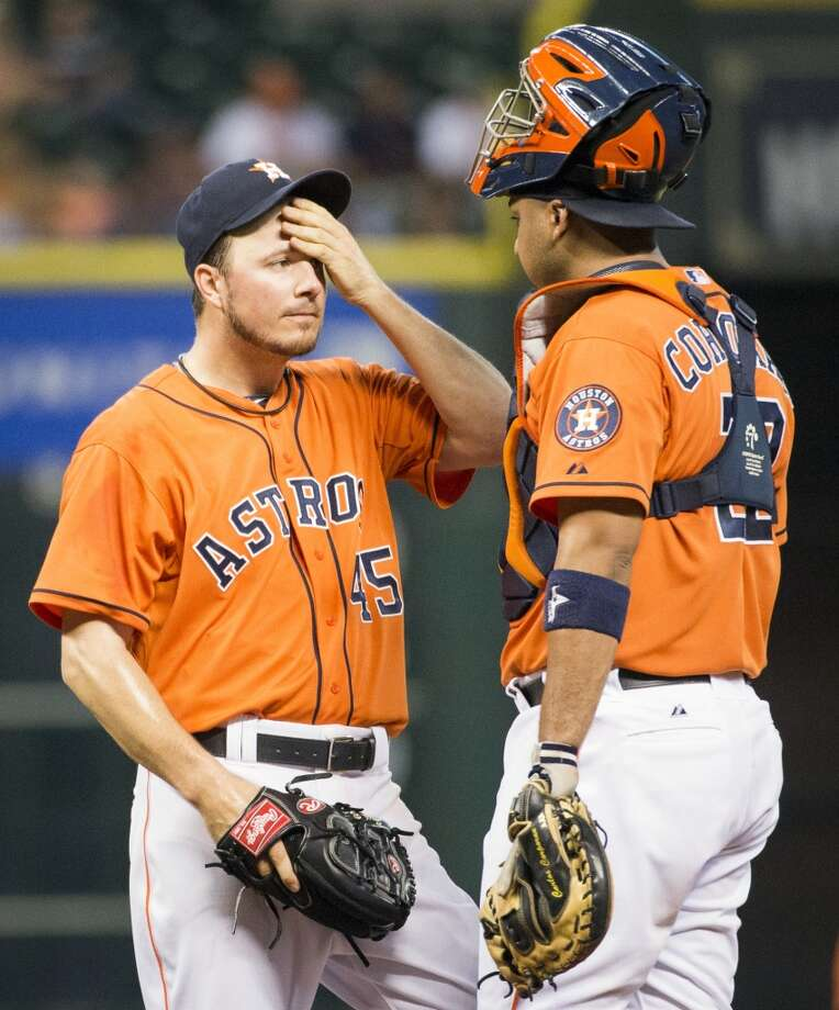 Astros starting pitcher Erik Bedard wipes his forehead as he gets a visit from catcher Carlos Corporan after giving up two runs during the first inning.