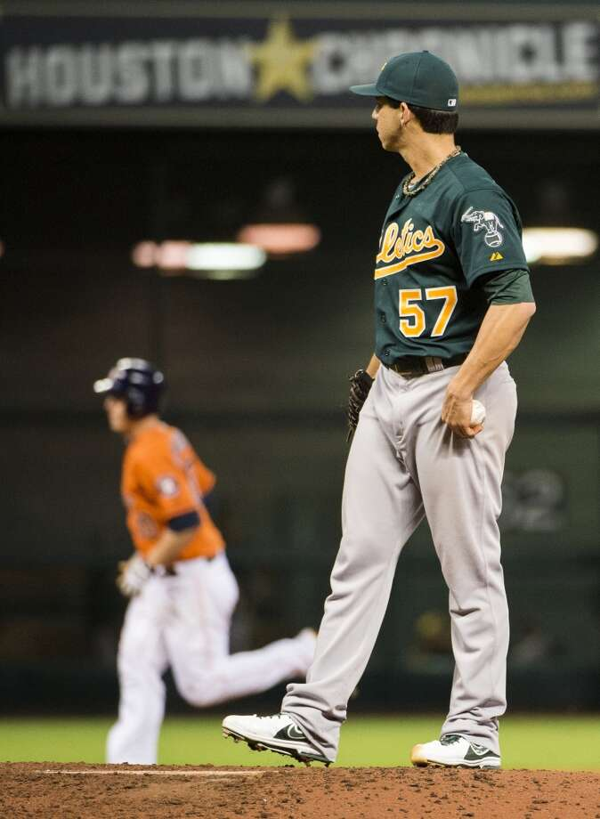 A's pitcher Tommy Milone looks on after Astros third baseman Matt Dominguez rounds the bases after hitting a solo home run.