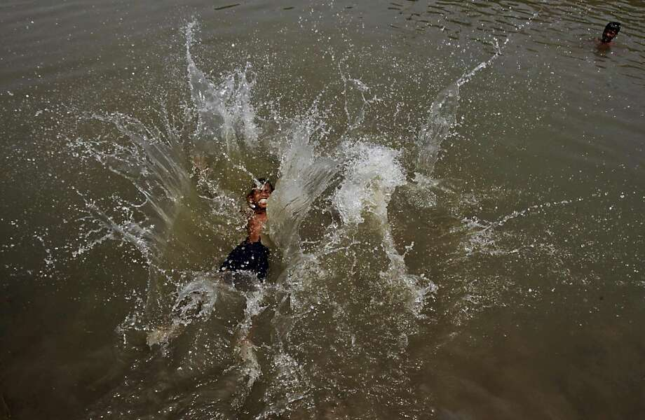 An Indian boy jumps into water with splash to cool off during a hot afternoon in Bhubaneswar, India, Friday, May 24, 2013. The heat wave condition intensified in the state with the mercury crossing 46 degrees Celsius (115 degrees Fahrenheit). (AP Photo/Biswaranjan Rout) Photo: Biswaranjan Rout, Associated Press