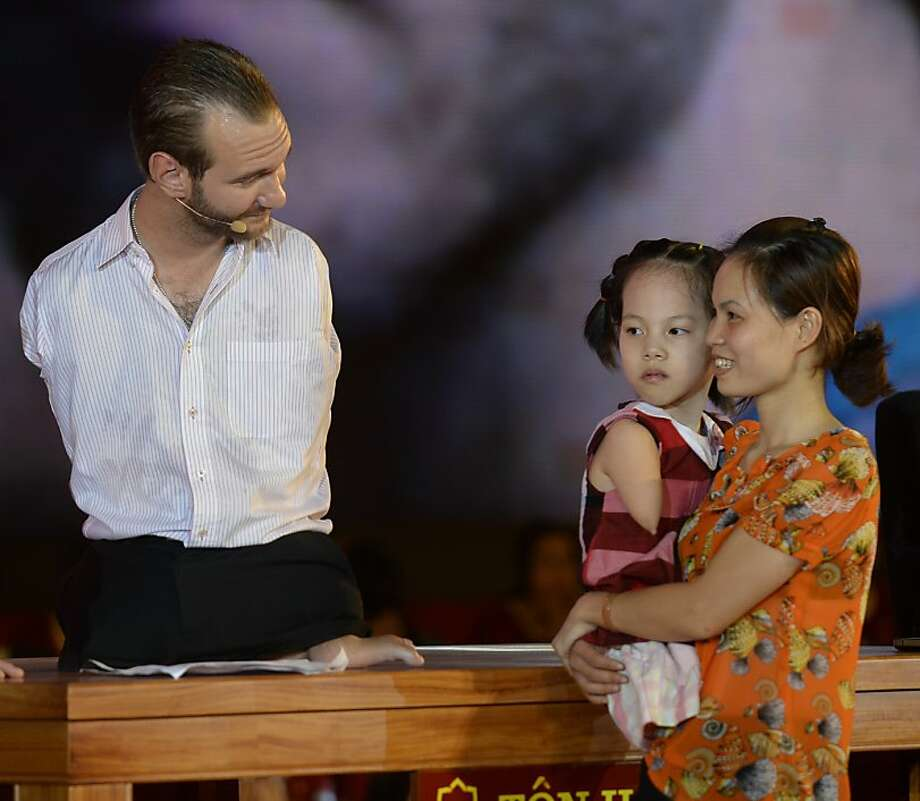 Australian motivational speaker Nick Vujicic (L) talks with 8-year-old disabled girl Linh Chi (C) and her mother as he addresses more than 20,000 people at Hanoi's My Dinh stadium on May 23, 2013. Like Vujicic, Linh Chi was born without legs and arms.  Vujicic  is on a four-day visit in Vietnam financed by a local private business to deliver speeches at different meetings with business people, students and disabled people in both Ho Chi Minh City and Hanoi. AFP PHOTO/HOANG DINH NamHOANG DINH NAM/AFP/Getty Images Photo: Hoang Dinh Nam, AFP/Getty Images