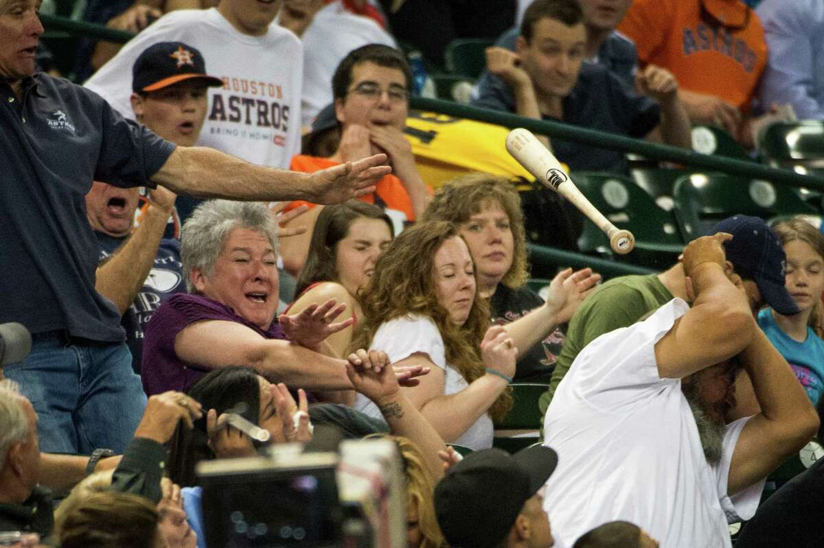 Fans behind the visiting dugout scatter as the bat of Oakland Athletics first baseman Nate Freiman flies into the stands during the fourth inning against the Houston Astros at Minute Maid Park on Friday, May 24, 2013, in Houston.