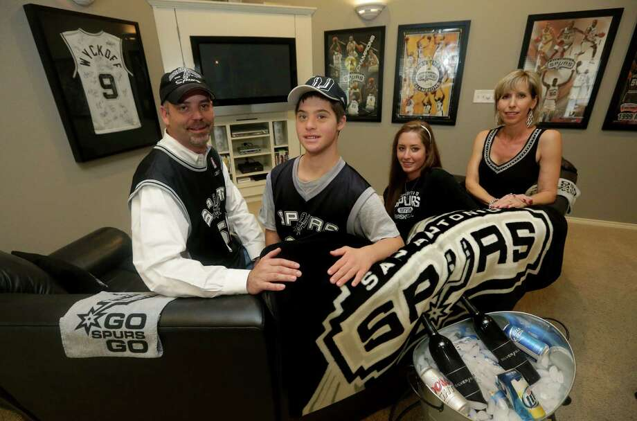 Todd Wyckoff (from left), son Cory, daughter Dusti Wyckoff and wife Polly have a Spurs-themed room where they can watch games. Photo: Photos By Bob Owen / San Antonio Express-News