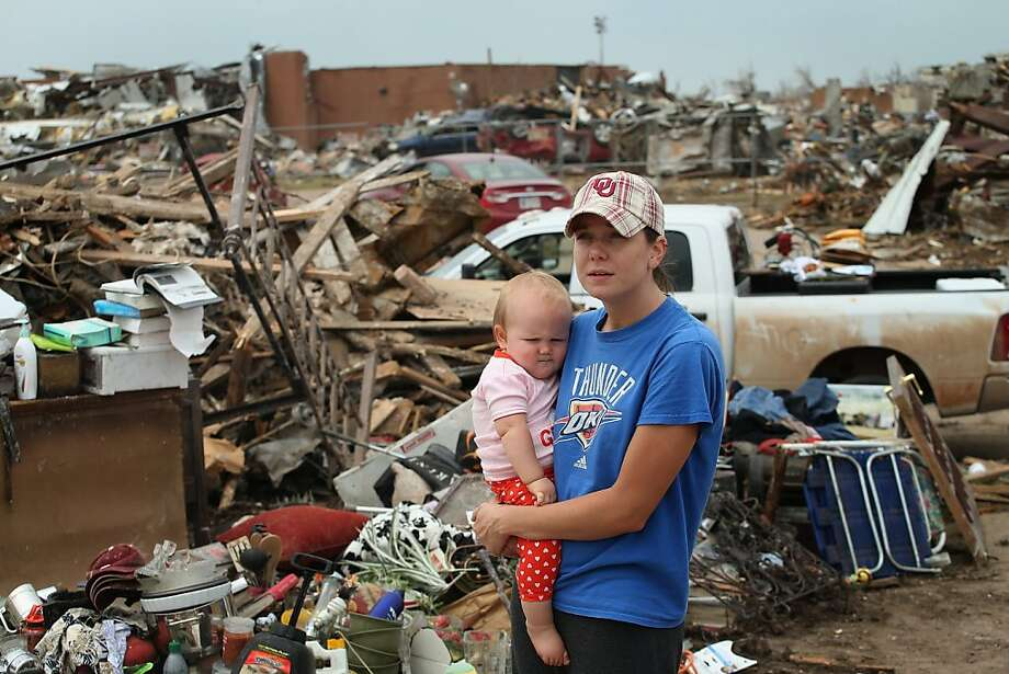 MOORE, OK - MAY 24:  Rebecca Smith holds her daughter Ashley while she looks over damage to her parent's home after it was destroyed by a tornado on May 24, 2013 in Moore, Oklahoma. The home is across the street from the Plaza Towers Elementary School (rear) were seven children died in the storm. A two-mile wide EF5 tornado touched down in Moore May 20 killing at least 24 people and leaving behind extensive damage to homes and businesses. U.S. President Barack Obama promised federal aid to supplement state and local recovery efforts.  (Photo by Scott Olson/Getty Images) Photo: Scott Olson, Getty Images