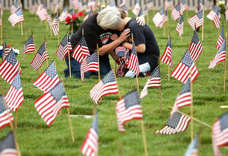 Fir Grove Elementary School fourth grader Brayden Corey, right, and grandmother Gayle Thomas of Roseburg, Ore.  share a moment at the grave of Jackie Thomas, Brayden's grandfather and Gayle's husband at the Roseburg National Cemetery, Friday, May 24, 2013. Jackie Thomas served in the Marine Corps and died in 2010.  Brayden Corey was at the cemetery to join classmates from Fir Grove Elementary School placing flags at headstones. (AP Photos/The News-Review, Michael Sullivan) Photo: Michael Sullivan, Associated Press