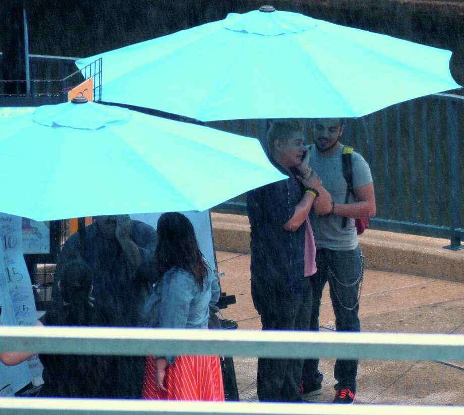 People find shelter from the rain under umbrellas along the Riverwalk on Friday, May 24, 2013. Photo: San Antonio Express-News
