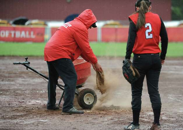 A Guilderland coach spreads dirt on infield puddles during a rainy Class AA quarterfinal softball game against Columbia on Friday, May 24, 2013 in Guilderland, N.Y.  (Lori Van Buren / Times Union) Photo: Lori Van Buren