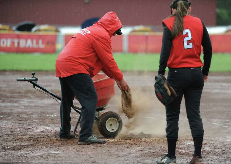A Guilderland coach spreads dirt on infield puddles during a rainy Class AA quarterfinal softball ga