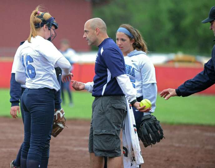 Columbia coach Chris Ciccone checks out the hand of his pitcher Haley Van Vorst after she got brushe