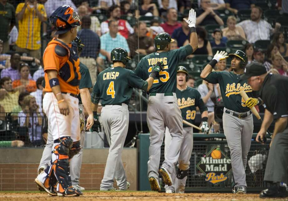 Astros catcher Carlos Corporan watches as A's center fielder Chris Young celebrates with teammates after hitting a three-run home run during the ninth inning.
