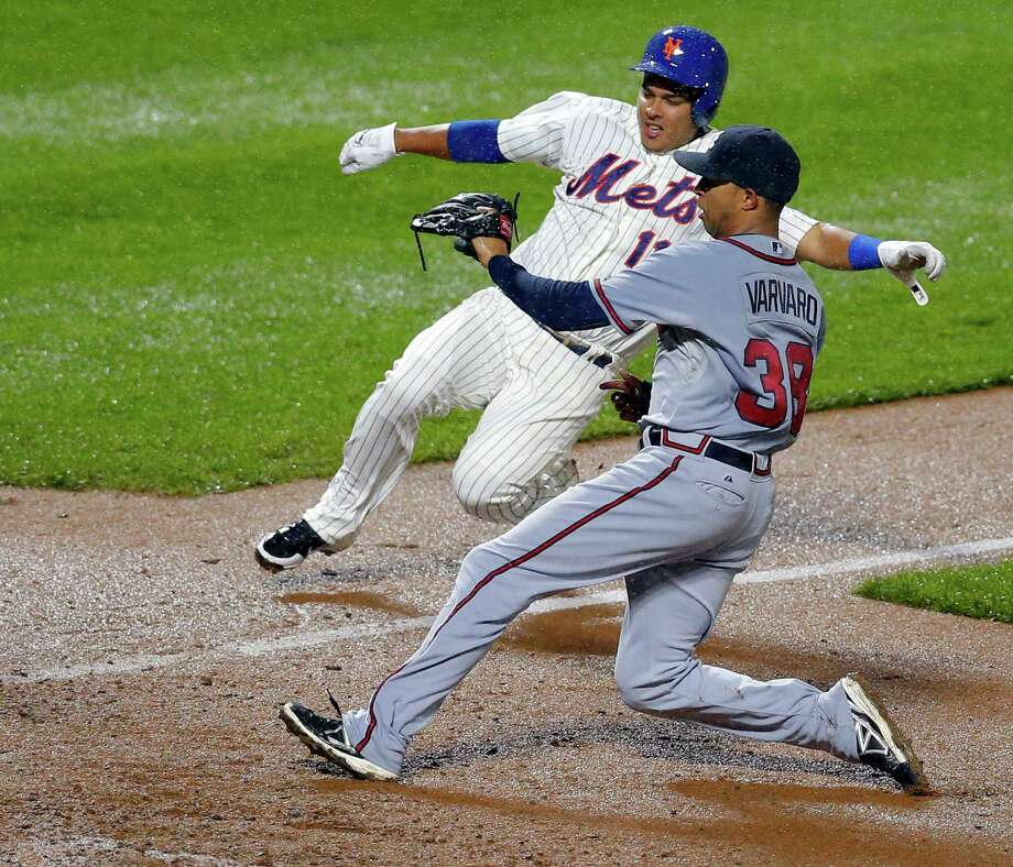Atlanta Braves relief pitcher Anthony Varvaro (38) runs in to cover the plate on a wild pitch in the rain as New York Mets' Ruben Tejada (11) slides home with the run that tied the game at 5-5 in the eighth inning before going into a rain delay during a baseball game at Citi Field in New York, Friday, May 24, 3013. (AP Photo/Paul J. Bereswill) Photo: Paul Bereswill