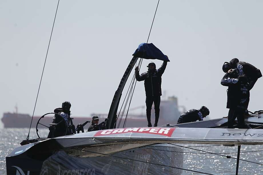 A member of the Emirates Team New Zealand removes a cover from the foil (center) of the AC72 before sailing on San Francisco Bay on  Friday, May 24, 2013 in San Francisco, Calif. Photo: Lea Suzuki, The Chronicle