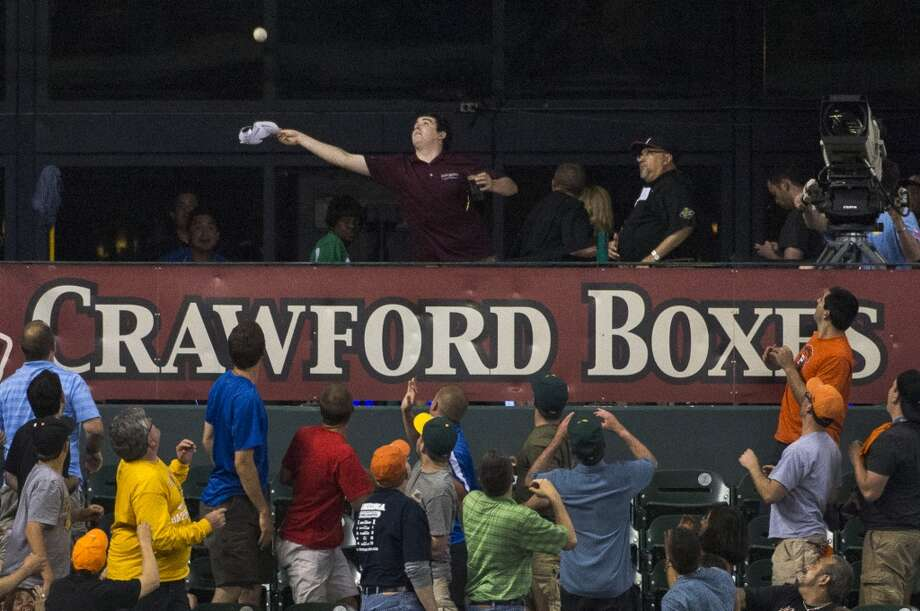 A fan in the Crawford Boxes tries to catch a home run off the bat of Astros third baseman Matt Dominguez during the fifth inning.