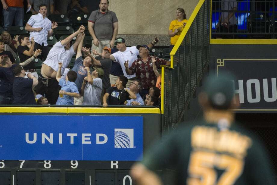 Athletics starting pitcher Tommy Milone (57) watches a fans try to catch a three-run homer by Houston Astros designated hitter J.D. Martinez during the fifth inning.