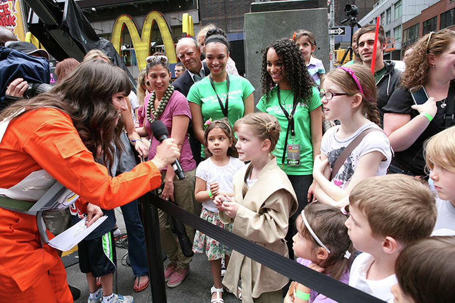 IMAGE DISTRIBUTED FOR LEGO SYSTEMS, INC. - Emcee Carly Henderson shares tips with local schoolchildren about 32 LEGO Model Builders spent over 17,000 hours and 5.3 million bricks to build the largest LEGO model ever revealed in New York City's Times Square, Thursday May 23, 2013. (Amy Sussman/AP Images for The LEGO Group) Photo: Amy Sussman, AP Images For LEGO Systems, Inc. / AP Images