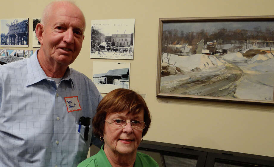 Bill and Nancy Gault stand near a painting of a gravel pit where Gault worked as a young man, part of a new exhibit about the Gault family at Westport Historical Society that opened Friday. Photo: Mike Lauterborn / Westport News contributed