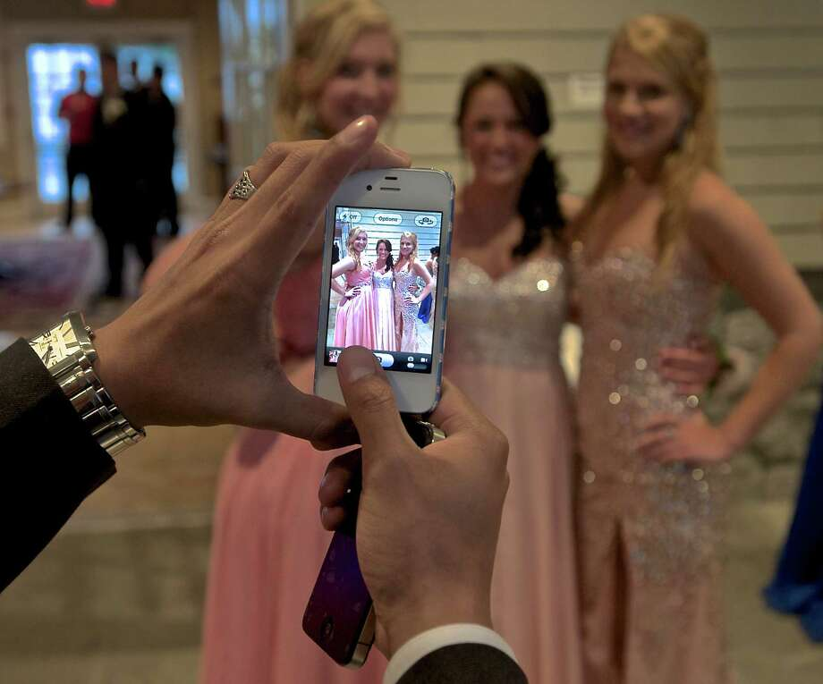 Seniors Ameila Furey, left, Kendall Krafick and Margaret Kaszycki, right, are photographed by Galo Moran during the Danbury High School senior prom held at the The Amber Room Colonnade, in Danbury, Conn. Friday May 24, 2013. Photo: H John Voorhees III