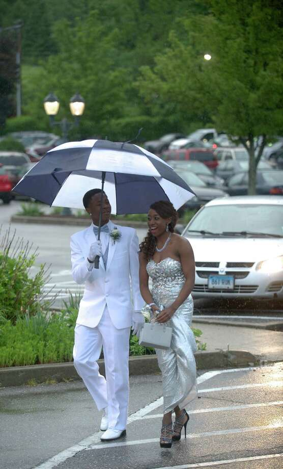 Akim Moffett holds an umbrella for his prom date Uniqua Tucker as they walk from the parking lot to the Danbury High School Senior Prom at the The Amber Room Colonnade, in Danbury, Conn. Friday May 24, 2013. Photo: H John Voorhees III