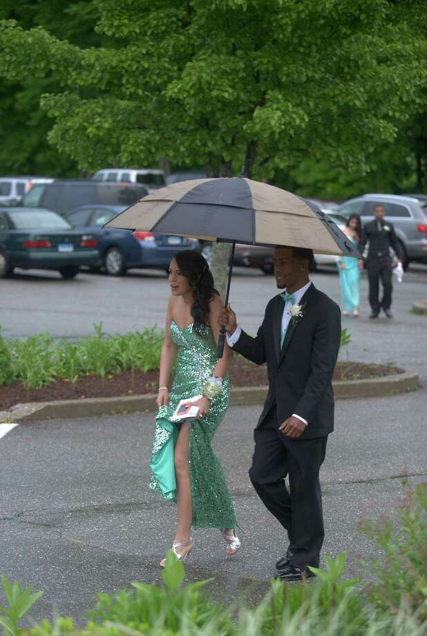 Rain meant dodging puddles and umbrellas as prom-goers made their way to the Danbury High School senior prom being held at the The Amber Room Colonnade, Danbury, Conn. Friday night May 24, 2013. Photo: H John Voorhees III