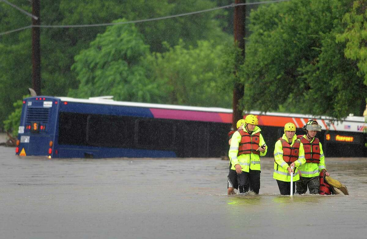 Fire department water rescue team members make their way through the water after checking a VIA bus that was flooded on McCullough just north of Basse. They found nobody in the bus on Saturday morning, May 25, 2013.