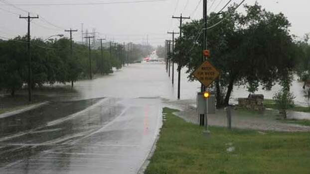 This is facing south on McCullough Avenue about 10 a.m. Saturday, with the Basse Road intersection in the distance. Olmos Creek spread to about a half mile. There appears to be a large stranded vehicle near Basse. The Olmos Basin Golf Course to the left of the avenue is inundated. Photo: John W. Gonzalez/ Express-News
