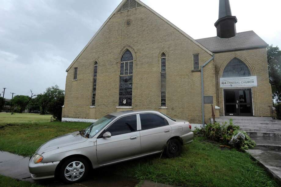 A car was washed onto the property of the SA Central Church on Woodlawn during heavy rains in San Antonio on Saturday morning, May 25, 2013. Photo: Billy Calzada, San Antonio Express-News / San Antonio Express-News