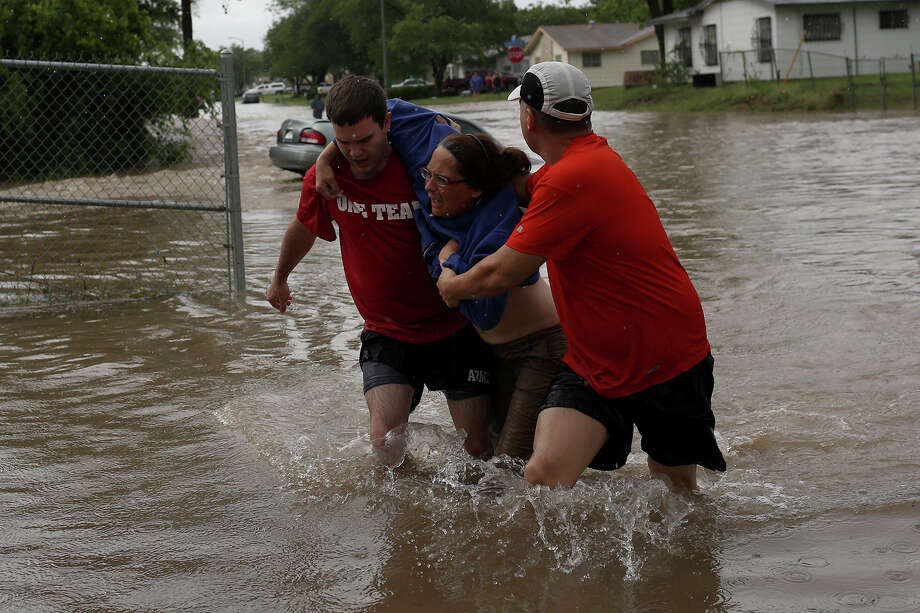 Marco Fairchild, left, and Gary Garza, right, help Sueann Schaller from her car after she drove it into floodwaters on Castleridge Dr. in the Westwood Village neighborhood off Military Dr. West on Saturday, May 25, 2013. Photo: Lisa Krantz, San Antonio Express-News / San Antonio Express-News