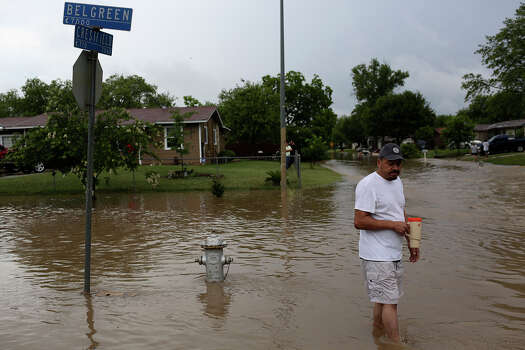 Alfredo Argumdo walks through flooded streets in the Westwood Village neighborhood off Military Dr. West on Saturday, May 25, 2013. Photo: Lisa Krantz, San Antonio Express-News / San Antonio Express-News