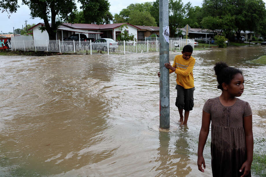 Jovan Hall, 12, and his sister, Inessa Hall, 8, check out the flooded intersection of Crestfield Street and Castleridge Dr. in the Westwood Village neighborhood off Military Dr. West on Saturday, May 25, 2013. Photo: Lisa Krantz, San Antonio Express-News / San Antonio Express-News