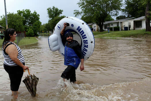 Albert Rios walks to his girlfriend, Nathasha Moreno, after he floated down Crestfield Dr. in the Westwood Village neighborhood off Military Dr. West on Saturday, May 25, 2013. Photo: Lisa Krantz, San Antonio Express-News / San Antonio Express-News