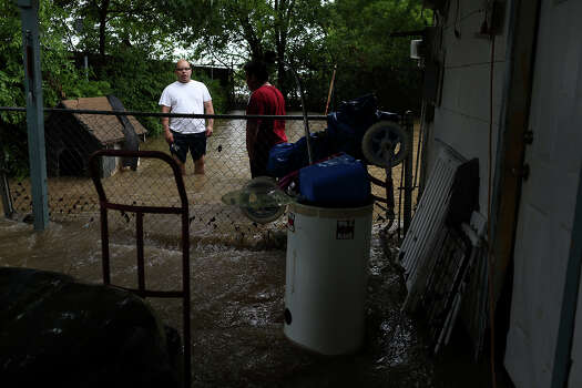 Raymond Bocanegra, left, talks with neighbors as he assess the damage to the home he rents on Castleridge Dr. in the Westwood Village neighborhood off Military Dr. West on Saturday, May 25, 2013. Photo: Lisa Krantz, San Antonio Express-News / San Antonio Express-News