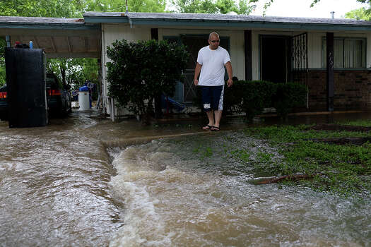 Raymond Bocanegra watches the water rushing through the yard of the home he rents with his wife and three children on Castleridge Dr. in the Westwood Village neighborhood off Military Dr. West on Saturday, May 25, 2013. The water was over a foot high coming in their home at the peak of the flooding and their backyard is completely flooded. Photo: Lisa Krantz, San Antonio Express-News / San Antonio Express-News