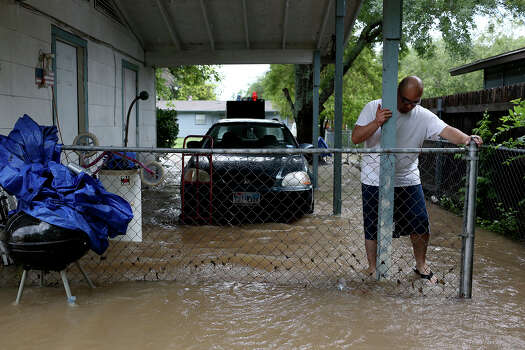 Raymond Bocanegra tries to clear debris as water continues to rush through the yard of the home he rents with his wife and three children on Castleridge Dr. in the Westwood Village neighborhood off Military Dr. West on Saturday, May 25, 2013. The water was over a foot high coming in their home at the peak of the flooding and their backyard is completely flooded. Photo: Lisa Krantz, San Antonio Express-News / San Antonio Express-News