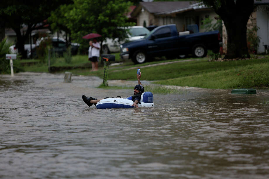 Albert Rios holds a beer as he floats on Crestfield Street  in the Westwood Village neighborhood off Military Dr. West on Saturday, May 25, 2013. Photo: Lisa Krantz, San Antonio Express-News / San Antonio Express-News