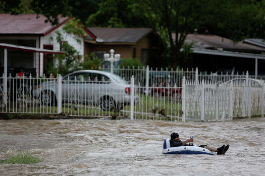 Albert Rios holds a beer as he floats into the intersection of Castleridge Dr. and Crestfield Street in the Westwood Village neighborhood off Military Dr. West on Saturday, May 25, 2013. Photo: Lisa Krantz, San Antonio Express-News / San Antonio Express-News