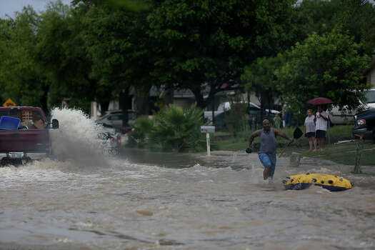 Edmond Mays runs towards his boat after a passing truck forced him out of it as he paddled down Crestfield Street in the Westwood Village neighborhood off Military Dr. West on Saturday, May 25, 2013. Photo: Lisa Krantz, San Antonio Express-News / San Antonio Express-News