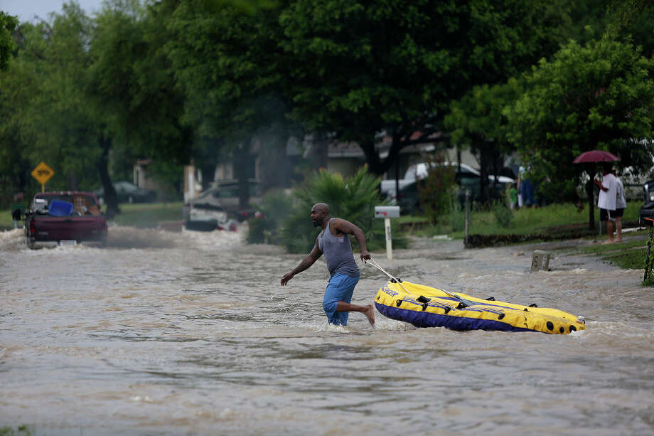 Edmond Mays pulls his boat after a passing truck forced him out of it as he paddled down Crestfield Street in the Westwood Village neighborhood off Military Dr. West on Saturday, May 25, 2013. Photo: Lisa Krantz, San Antonio Express-News / San Antonio Express-News