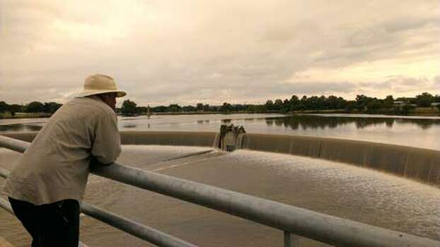 Frank Sanchez checks out the floodwaters flowing over the dam at Woodlawn Lake. Photo: John Tedesco/Express-News