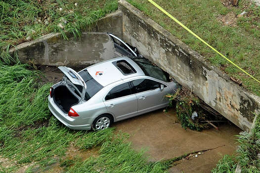 A car is lodged where rushing waters took it on Rhapsody near 281 during heavy rains in San Antonio on Saturday morning, May 25, 2013. The occupant died in the incident. Photo: Billy Calzada, San Antonio Express-News / San Antonio Express-News