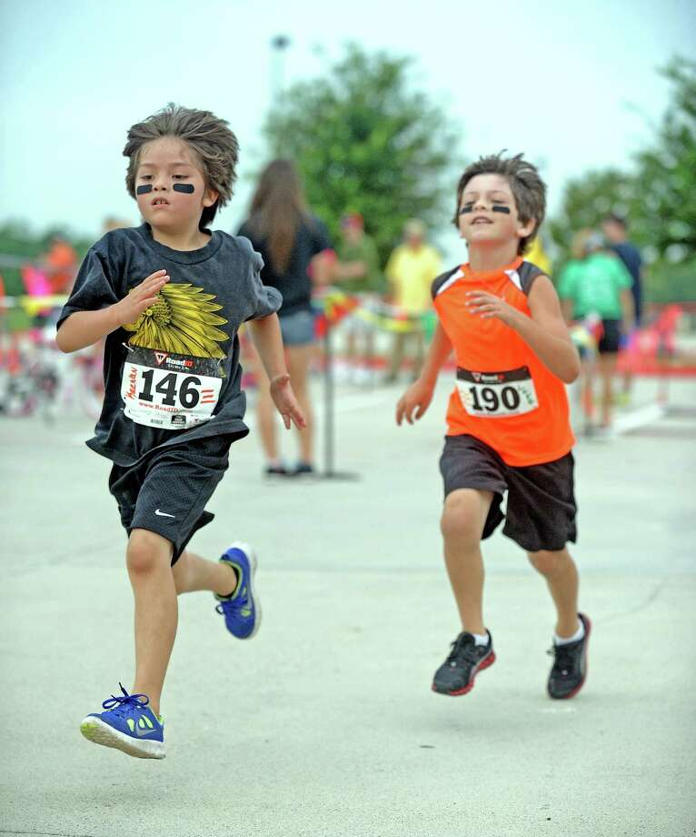 "Keenan De La O, left, and Luke Williams, right, take off sprinting on their last lap of the 2013 Daisies and Dragons Duathlon For Kids on Saturday, May 25, 2013, in Beaumont at the BISD Dr. Carroll ""Butch"" Thomas Educational Resource Center. Photo taken: Randy Edwards/The Enterprise"
