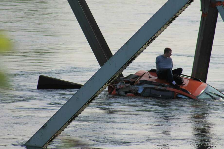 A man sits on his car after an Interstate 5 bridge collapsed over the Skagit River between Mt. Vernon and Burlington on Thursday, May 23, 2013. Two cars and one travel trailer went in the water. There were no known fatalities. Photo: Francisco Rodriguez, Special To Seattlepi.com / special to seattlepi.com