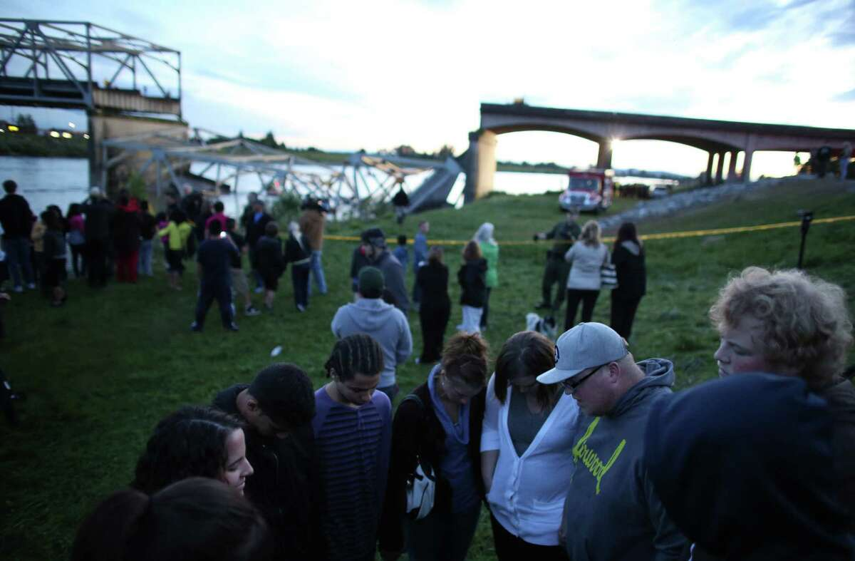 People offer spontaneous prayer after an Interstate 5 bridge collapsed over the Skagit River between Mt. Vernon and Burlington on Thursday, May 23, 2013. Two cars and one travel trailer went in the water. There were no know fatalities.