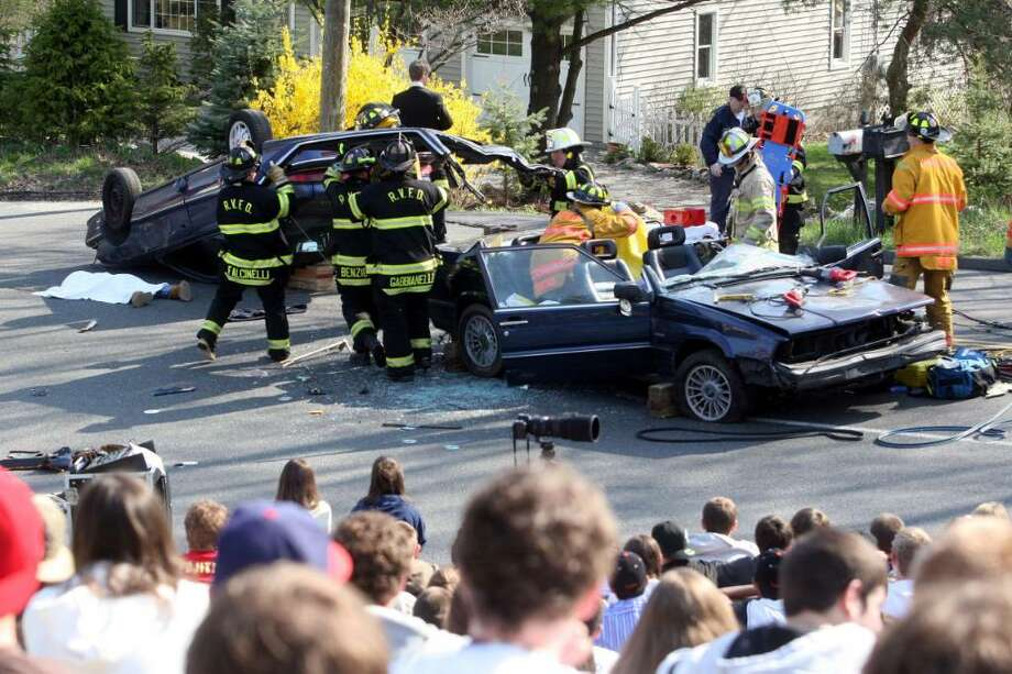 Ridgefield Firefighters remove the roof of a car during a mock car accident to show the dangers of drunk driving at Ridgefield High School April 23, 2008. (Karen Vibert-Kennedy) Photo: File Photo / The News-Times File Photo